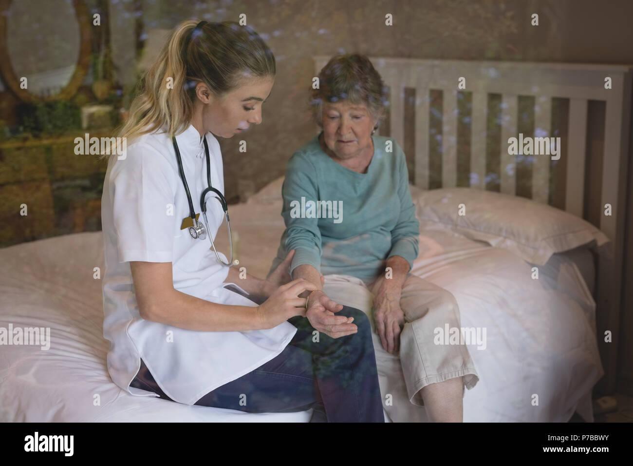 Physiotherapist examining a senior woman - Stock Image