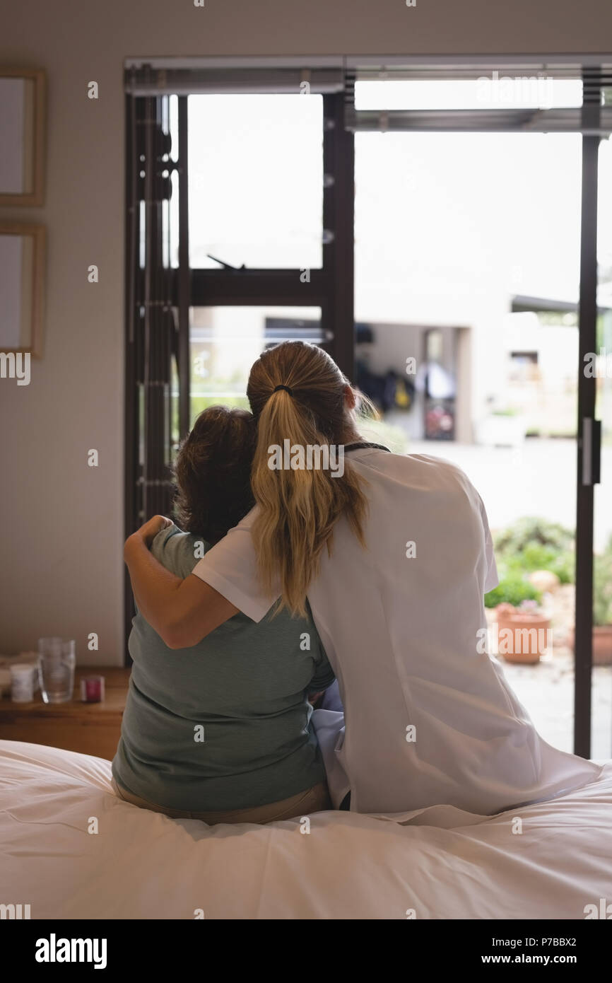 Physiotherapist embracing senior woman at home - Stock Image