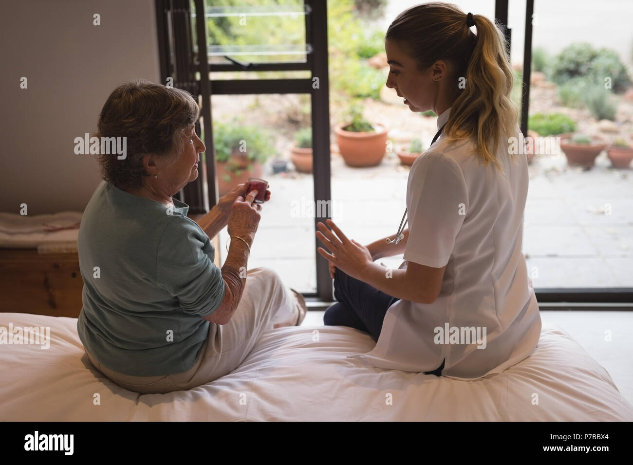 Physiotherapist discussing with a senior woman - Stock Image