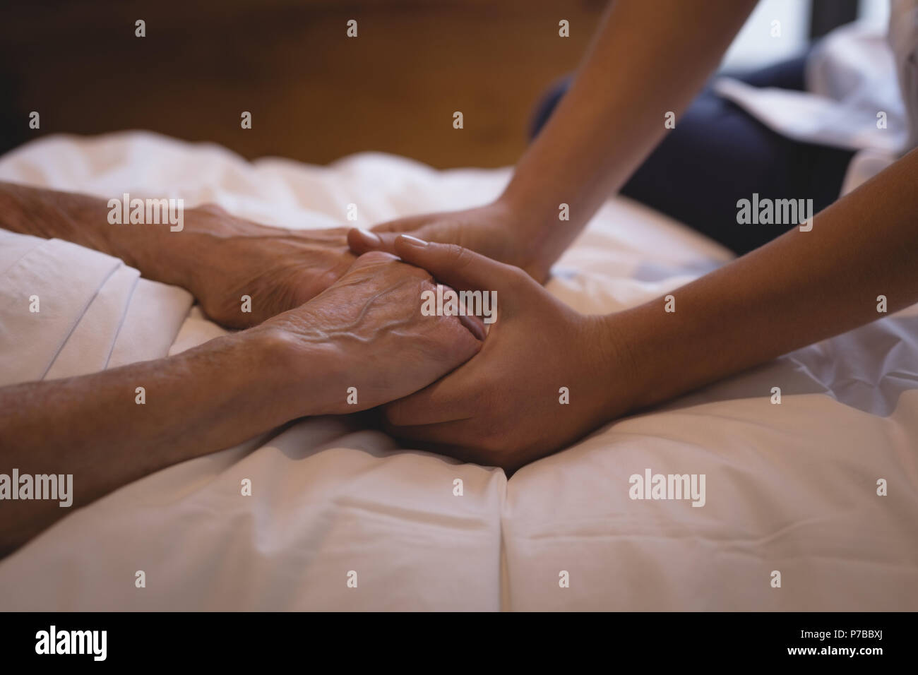 Physiotherapist holding hand of a senior woman - Stock Image