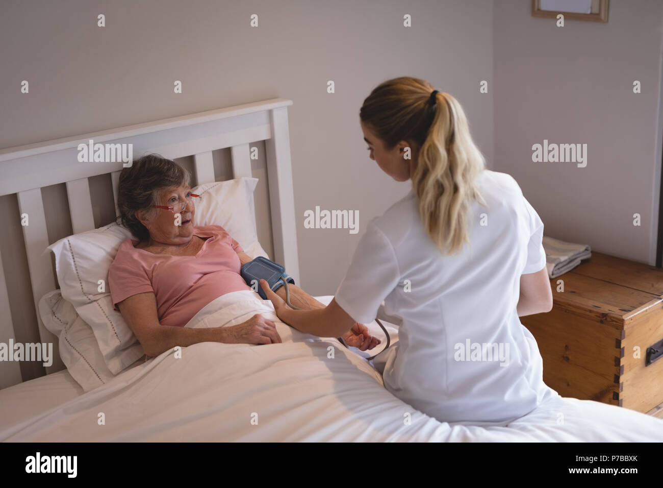 Physiotherapist checking blood pressure of senior woman Stock Photo