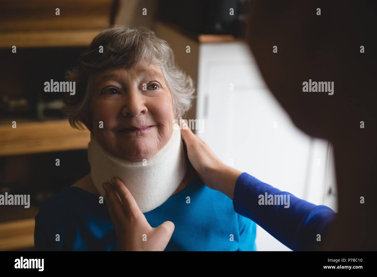 Physiotherapist setting cervical collar on senior woman - Stock Image