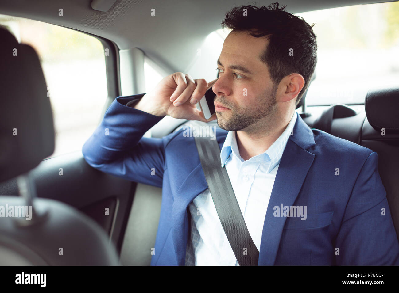 Businessman talking on mobile phone in a car - Stock Image