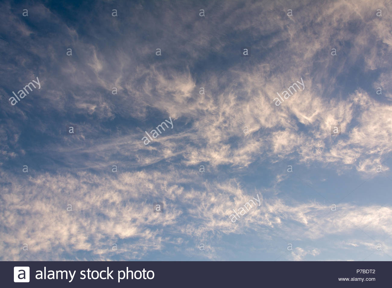 Beautiful cloud patterns set off by a blue sky - Stock Image