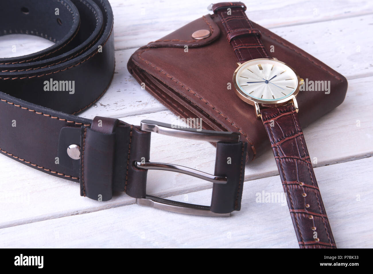 Men's accessories for business and rekreation. Leather belt, wallet, watch and smoking pipe on wood background.. Top view composition. - Stock Image
