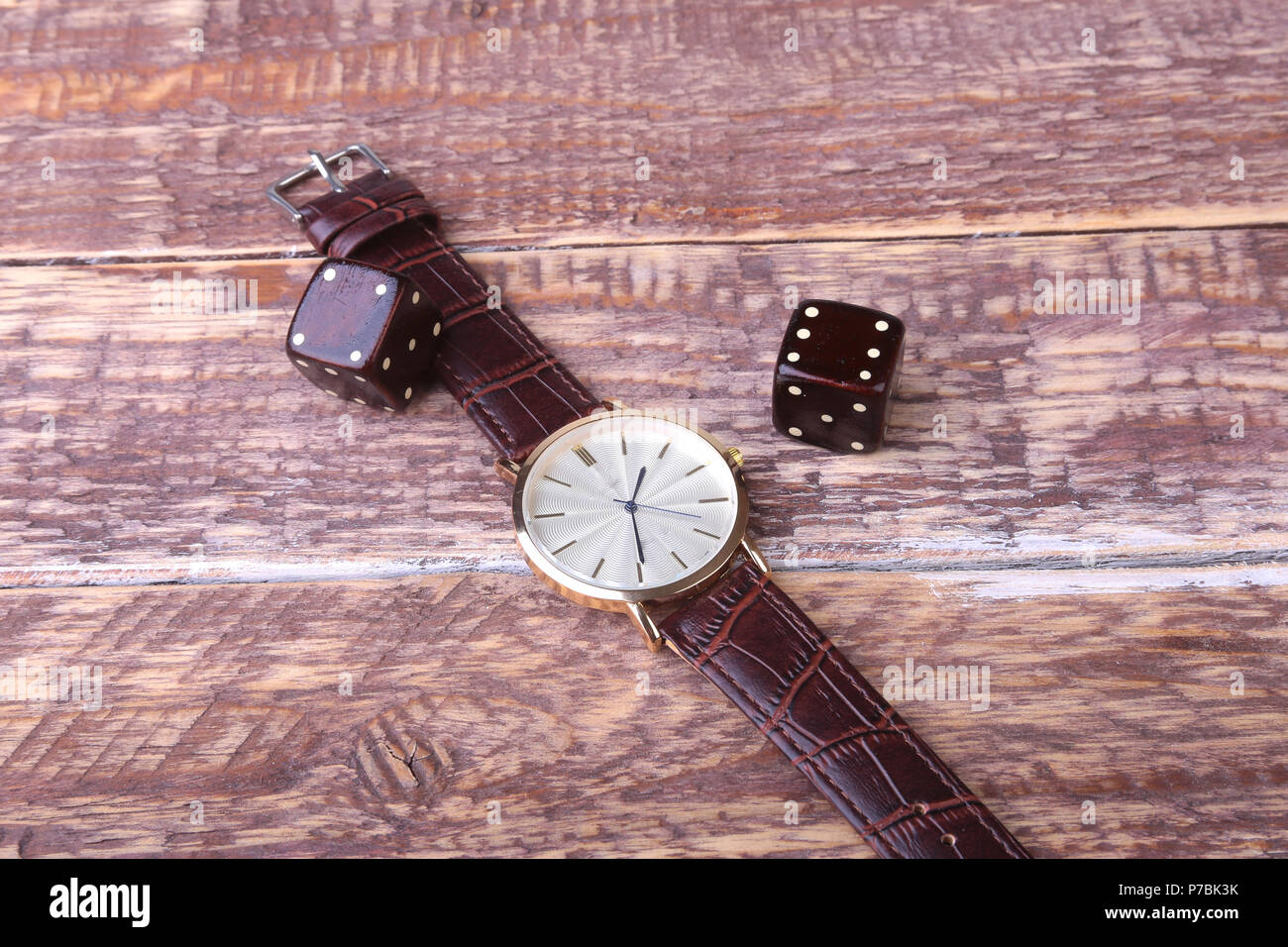Men's accessories for business and rekreation. Watch and dice on wood background.. Top view composition. - Stock Image