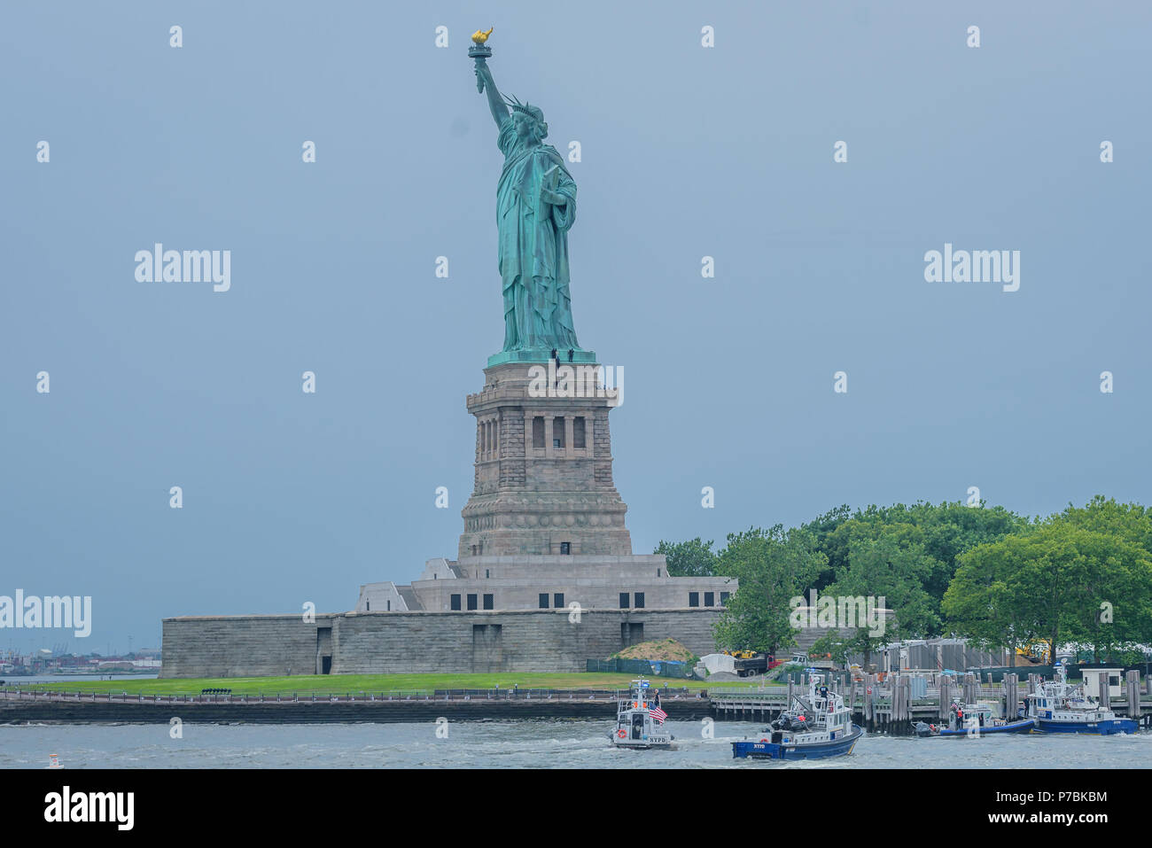 "New York, United States. 04th July, 2018. Liberty Island was evacuated because of a person climbing the Statue of Liberty's base on the Fourth of July shortly after seven protesters who unfurled an ""Abolish ICE"" banner from the statue's pedestal calling for abolishing Immigration and Customs Enforcement were arrested. Credit: Erik McGregor/Pacific Press/Alamy Live News Stock Photo"