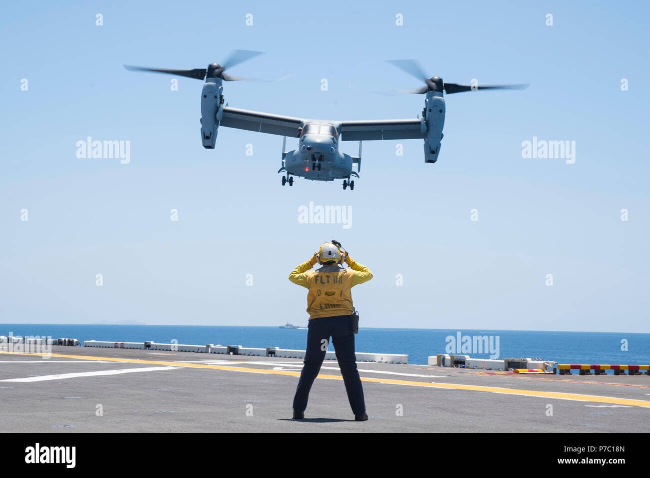 """180703-N-RD713-186 PACIFIC OCEAN,  (July 3, 2018) Aviation Boatswain's Mate (Handling) 3rd Class Tiffanie Allenderriley, from Joplin, Mo., signals an MV-22B Osprey, assigned to the """"Red Lions"""" of Marine Medium Tiltrotor Squadron (VMM) 363, for landing on the flight deck of the amphibious assault ship USS Bonhomme Richard (LHD 6). Bonhomme Richard is currently underway in the U.S. 3rd Fleet area of operations. (U.S. Navy photo by Mass Communication Specialist 3rd Class Zachary DiPadova) Stock Photo"""
