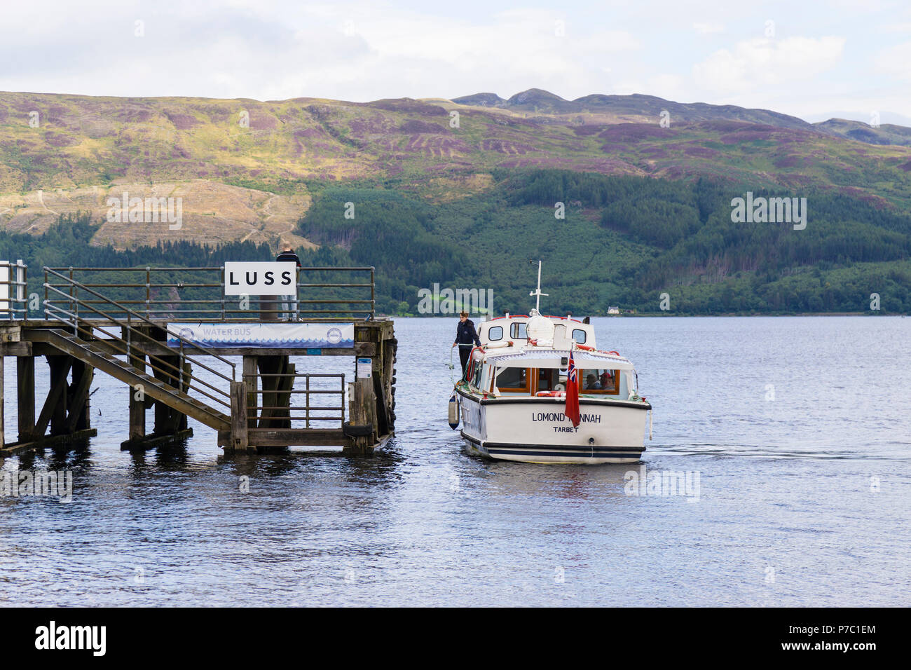 Tourist boat at the jetty at Luss on Loch Lomond. Luss has been named as the most beautiful village in Scotland. - Stock Image