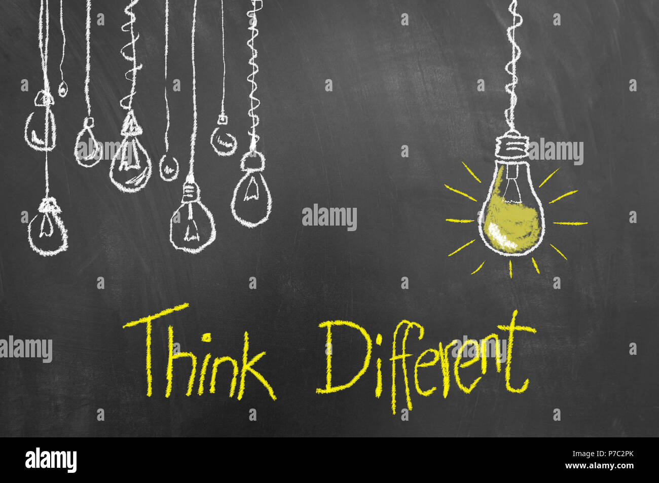 Think different concept with light bulbs drawing and text on chalkboard or blackboard as innovation creativity new vision concept - Stock Image