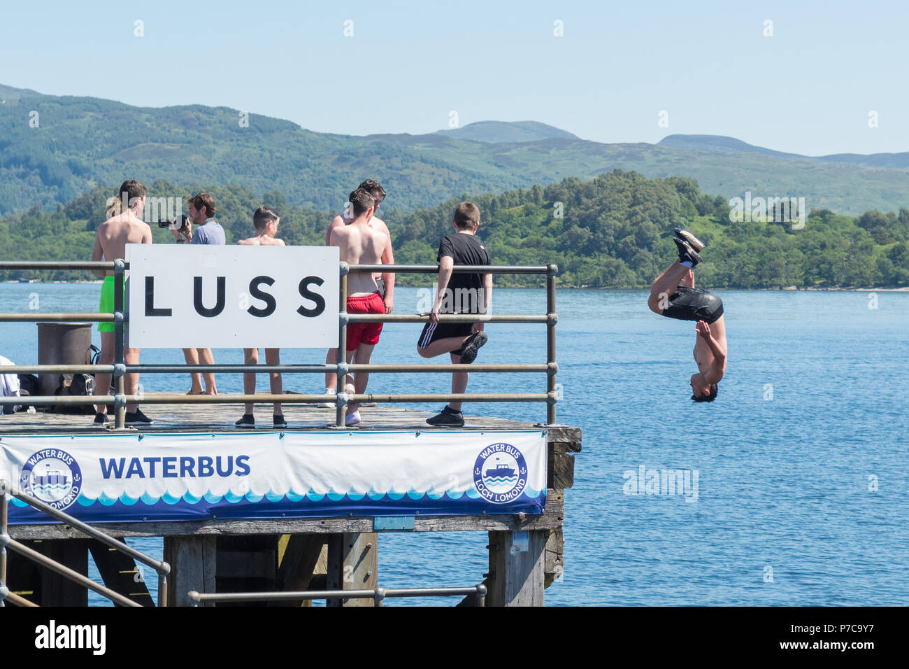 diving and somersaulting off Luss Pier into Loch Lomond during hot weather, Scotland, UK - Stock Image