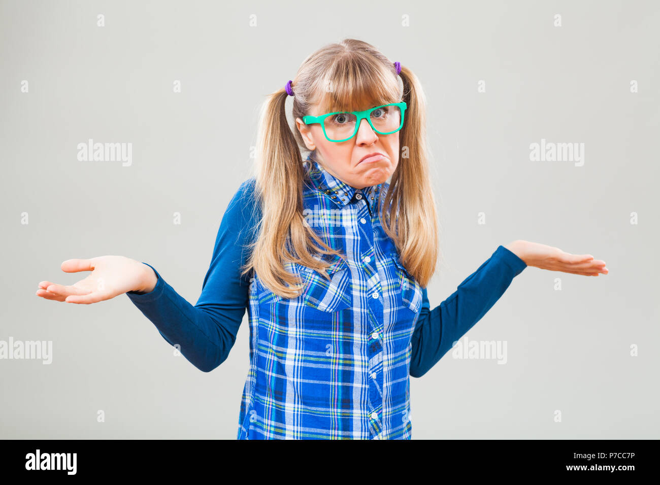 Studio shot portrait of confused nerdy woman - Stock Image
