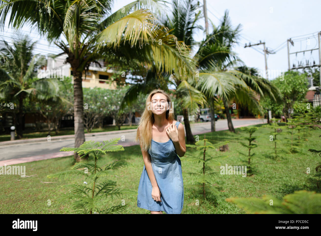 Young smiling woman wearing jeans sundress and standing near palms in background. - Stock Image