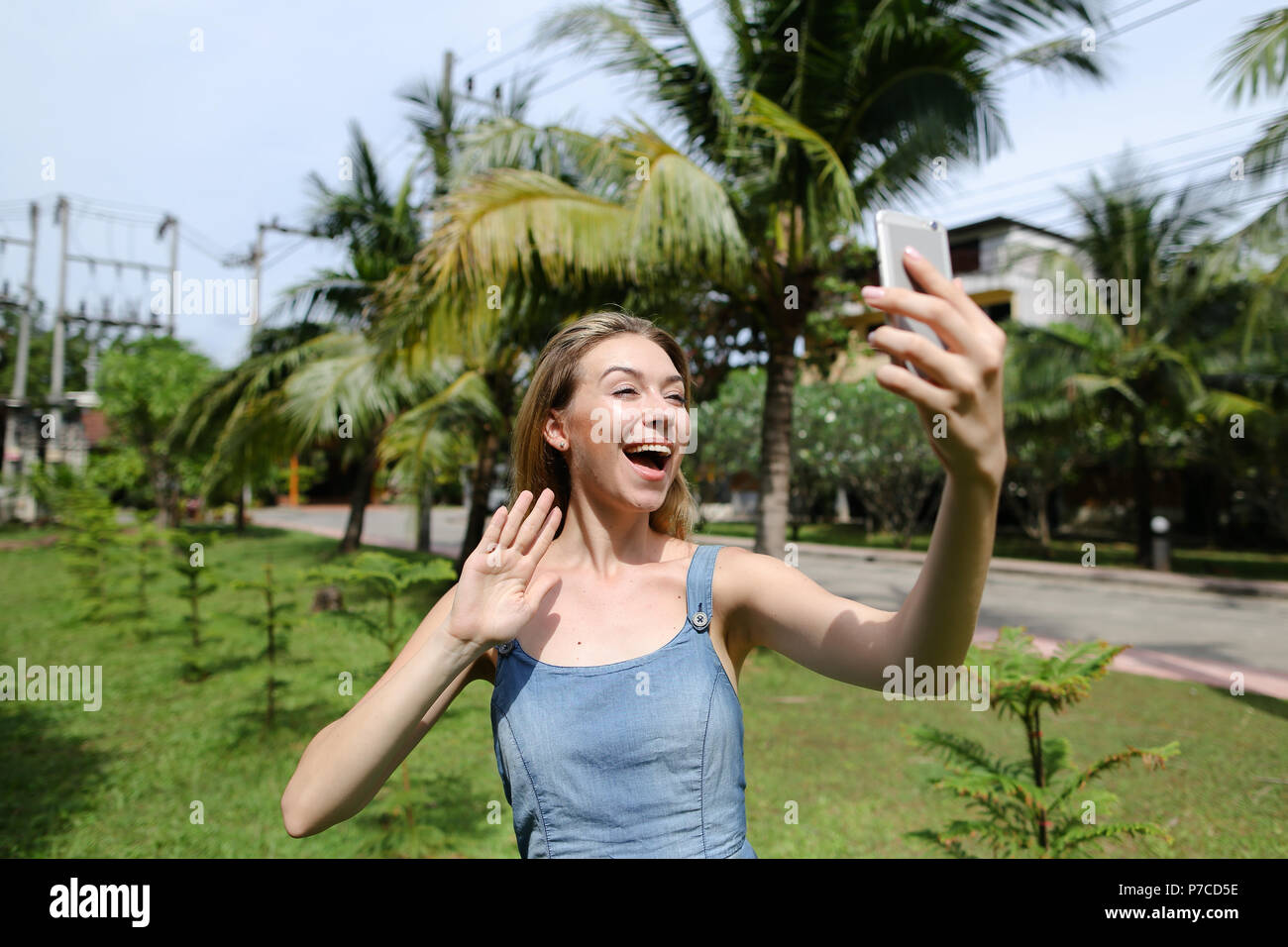Young girl making video call by smartphone near palm trees in background. - Stock Image