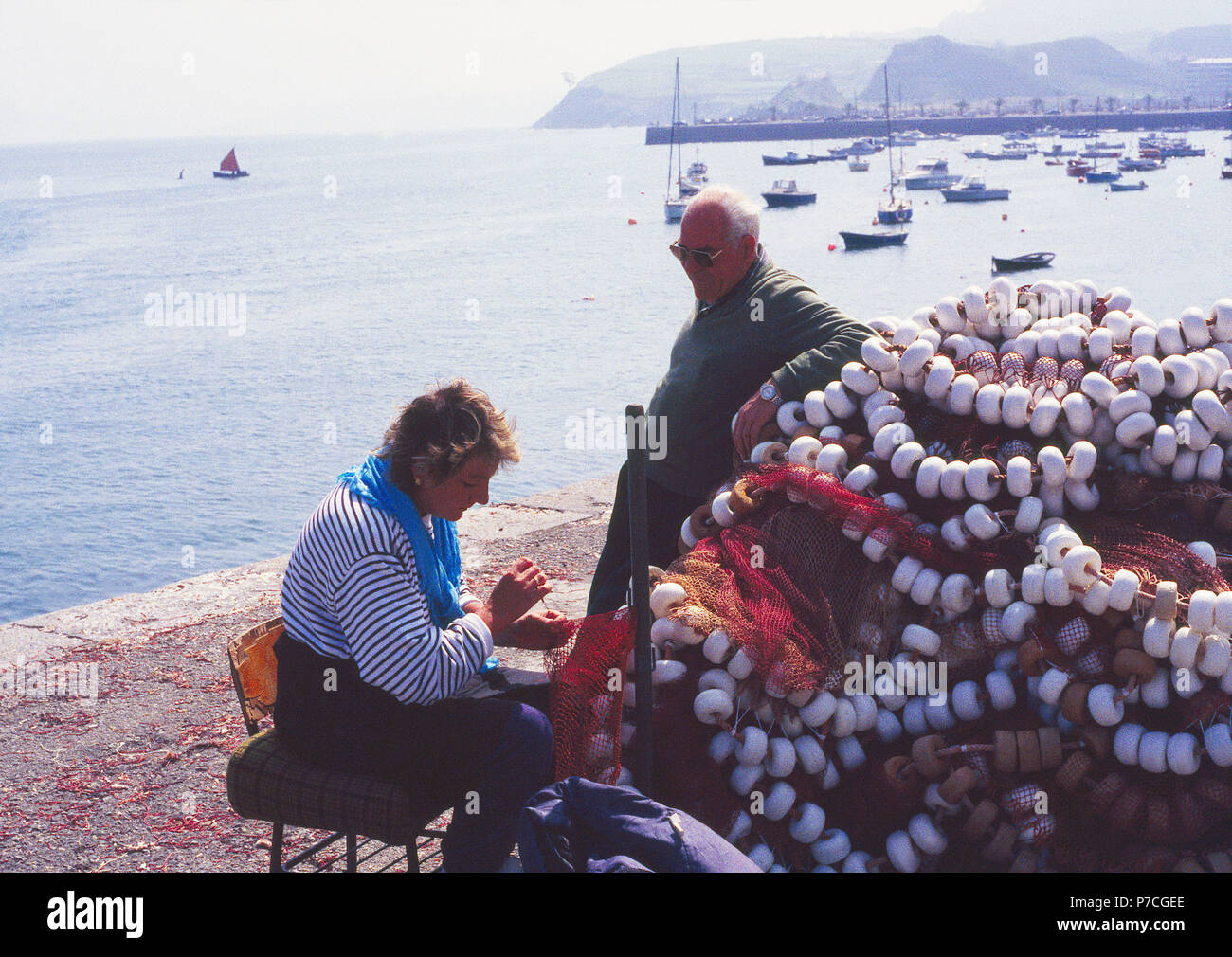 Woman sewing fishing nets at the harbour. Castro Urdiales, Cantabria, Spain. - Stock Image