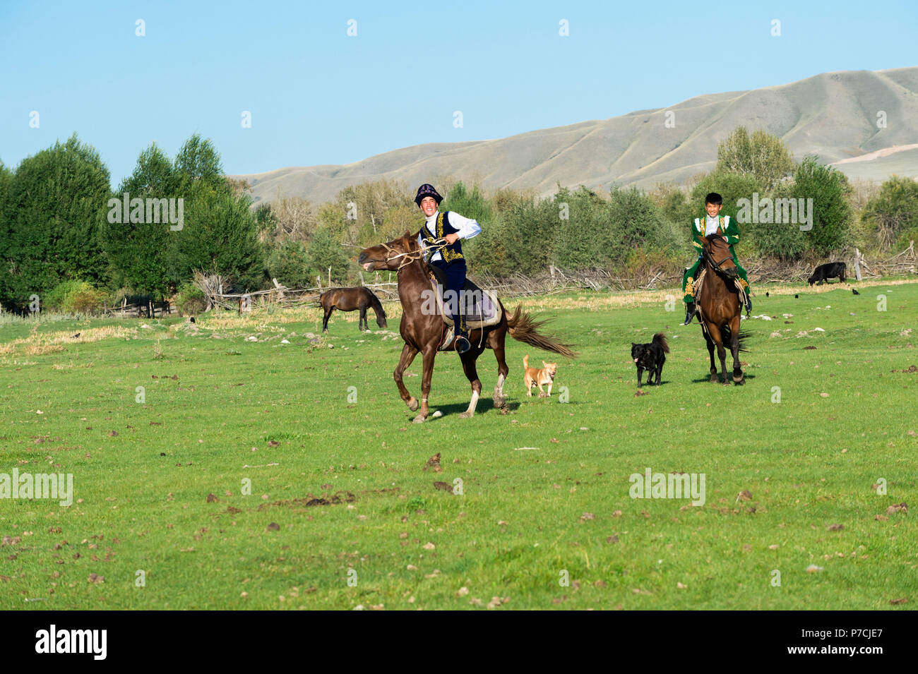 Two Kazakh riders in traditional clothes, Sati village, Tien Shan Mountains, Kazakhstan - Stock Image