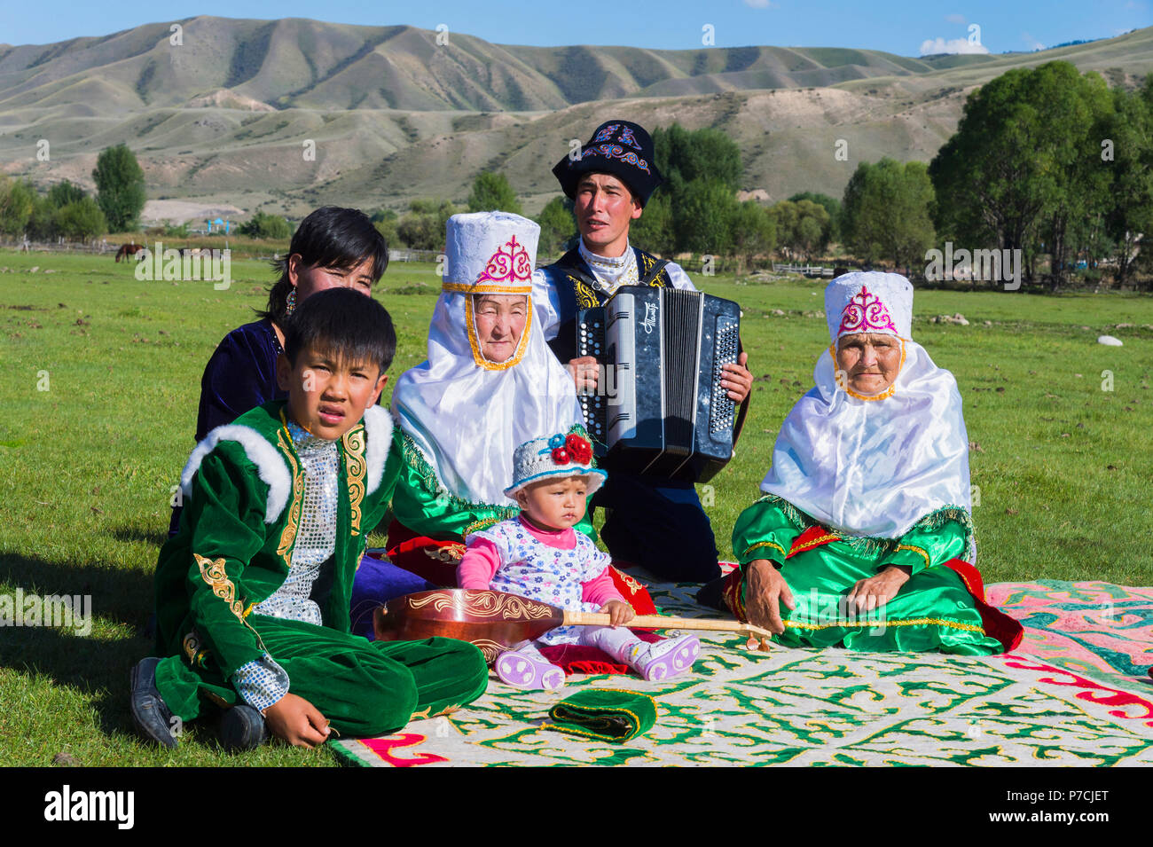 Kazakh family in traditional clothes, listening to accordion player, For editorial Use only, Sati village, Tien Shan Mountains, Kazakhstan Stock Photo