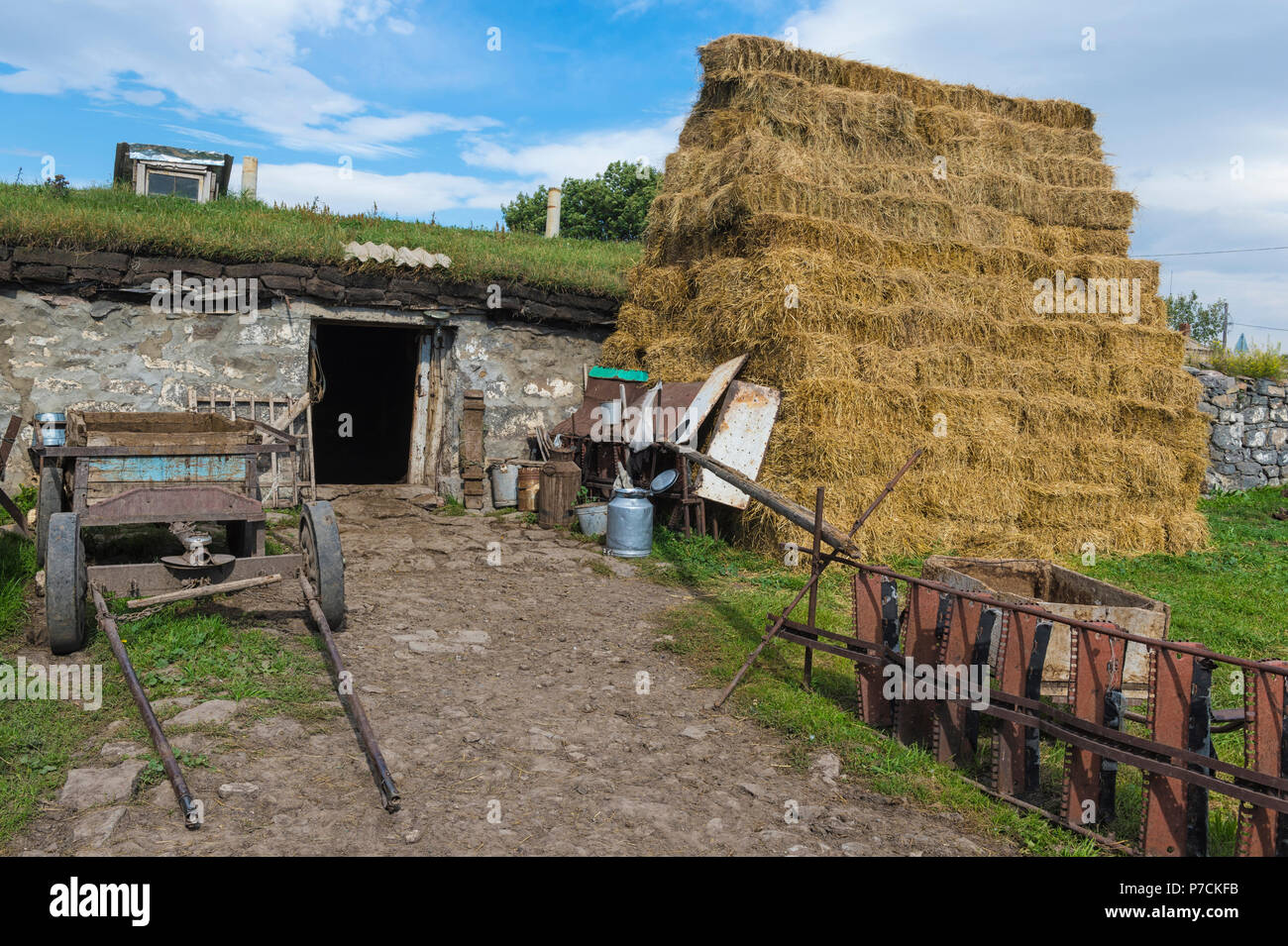 Old agricultural equipment, haystack and countryside house, Bokdajeni village, Georgia - Stock Image