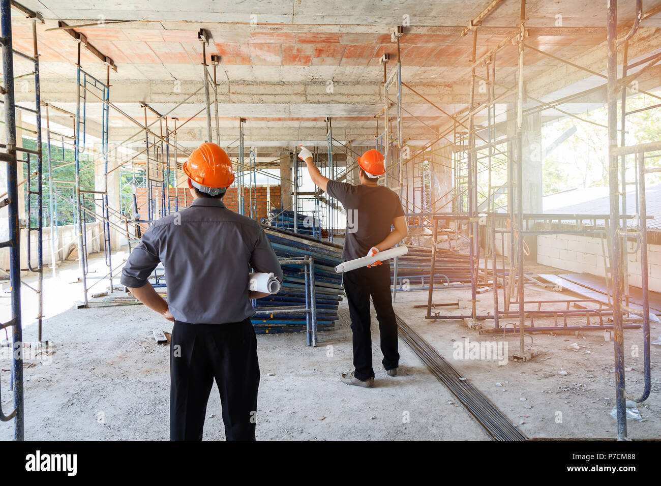 Engineer discussing with foreman about project in building construction site Stock Photo