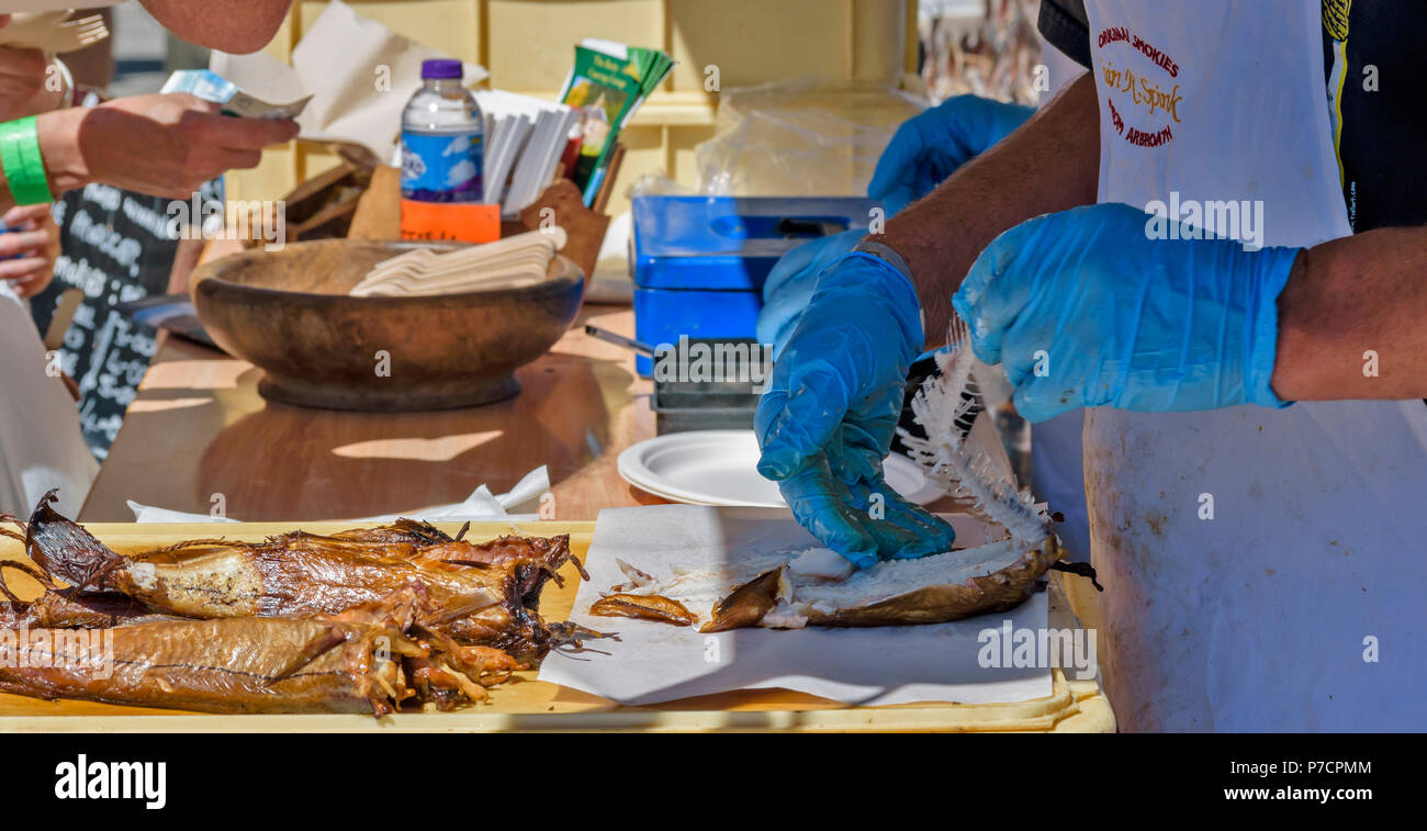 PORTSOY FESTIVAL ABERDEENSHIRE SCOTLAND ARBROATH SMOKIES HADDOCK REMOVING THE BACKBONE FROM THE SMOKED AND COOKED FISH - Stock Image