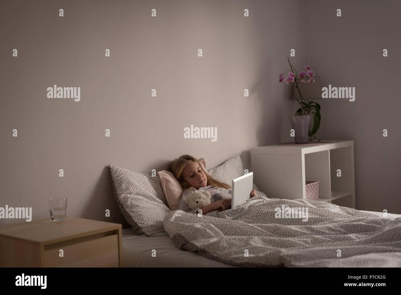 Girl using digital tablet in bedroom - Stock Image