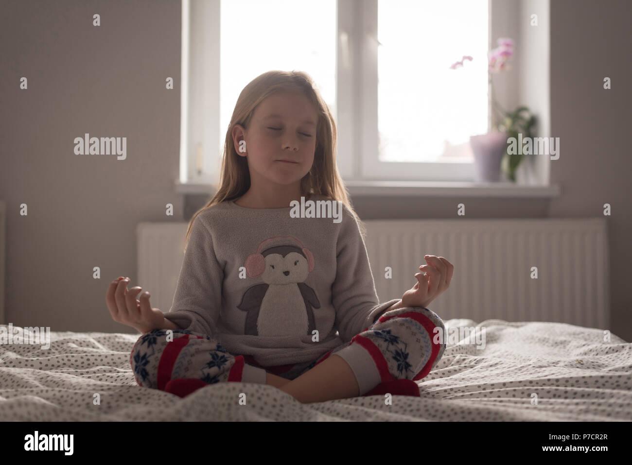 Girl performing yoga in bedroom - Stock Image