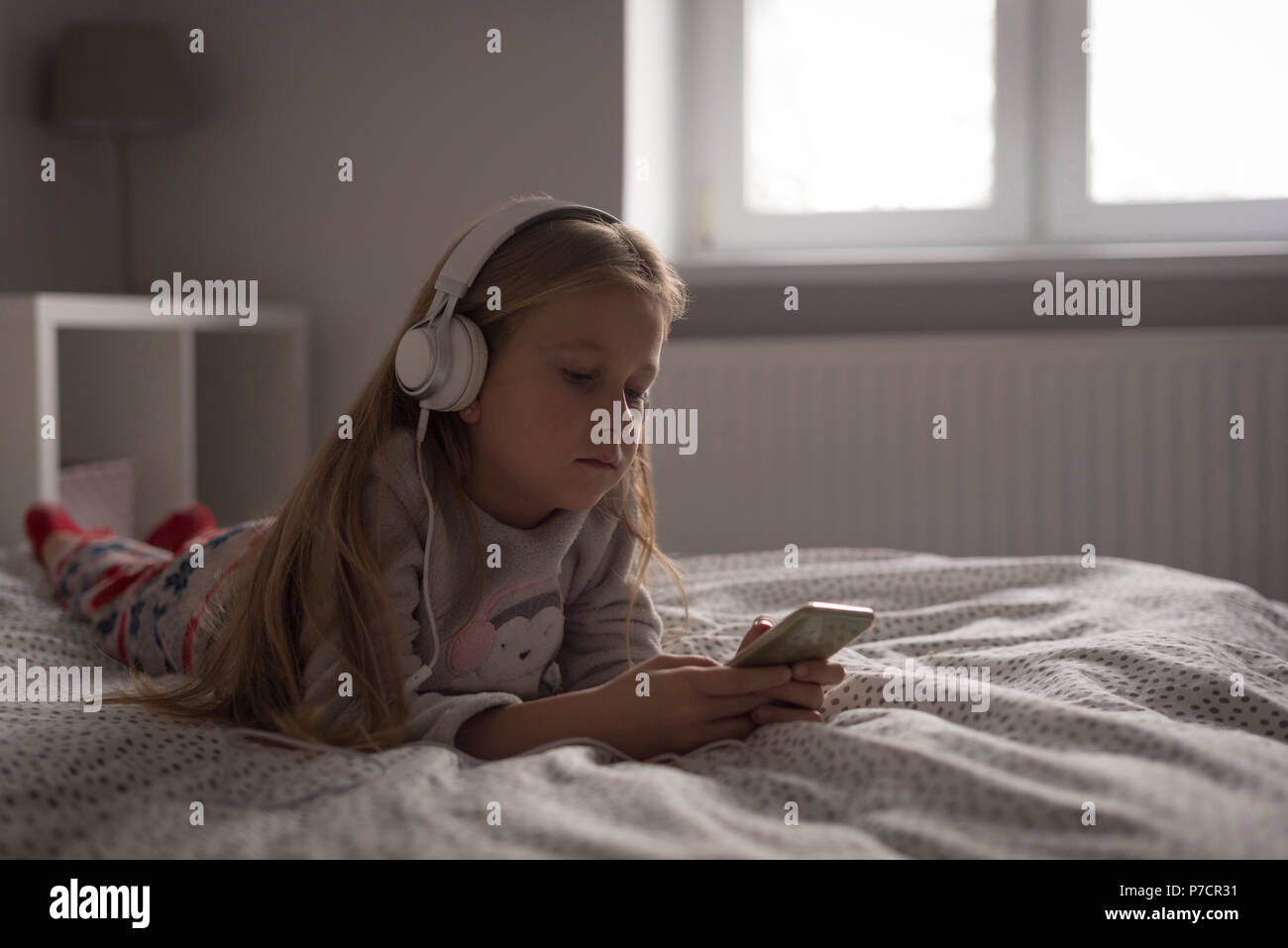Girl listening music on mobile phone with headphones in bedroom - Stock Image