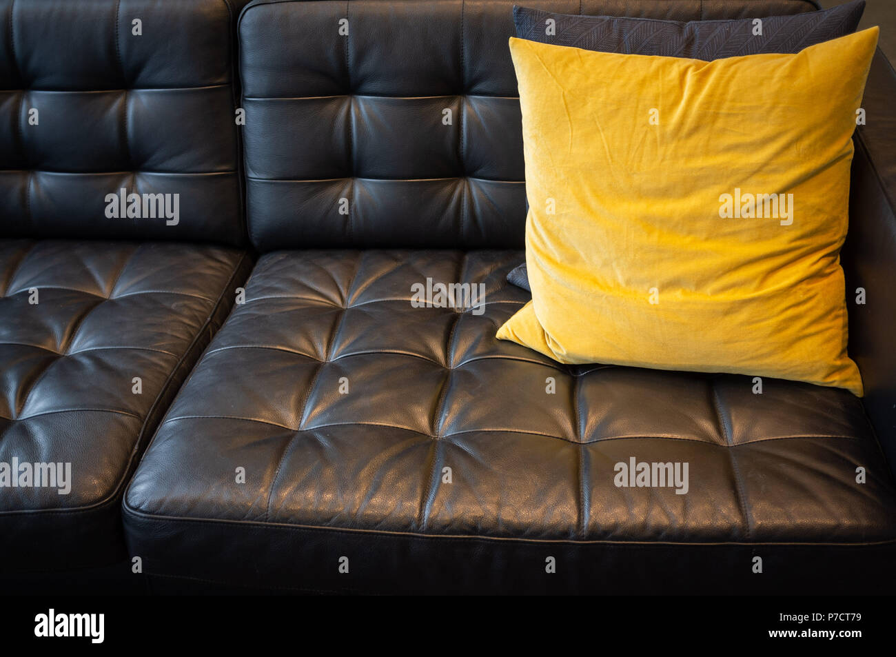 Yellow Pillow On Black Leather Couch Closeup Stock Photo Alamy