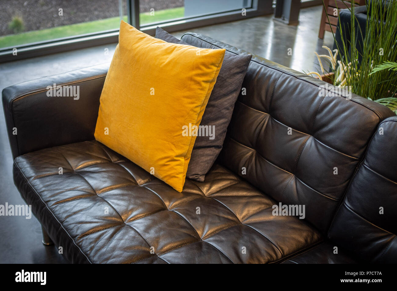 Pillows On Black Leather Couch Interior Design Sample Stock Photo