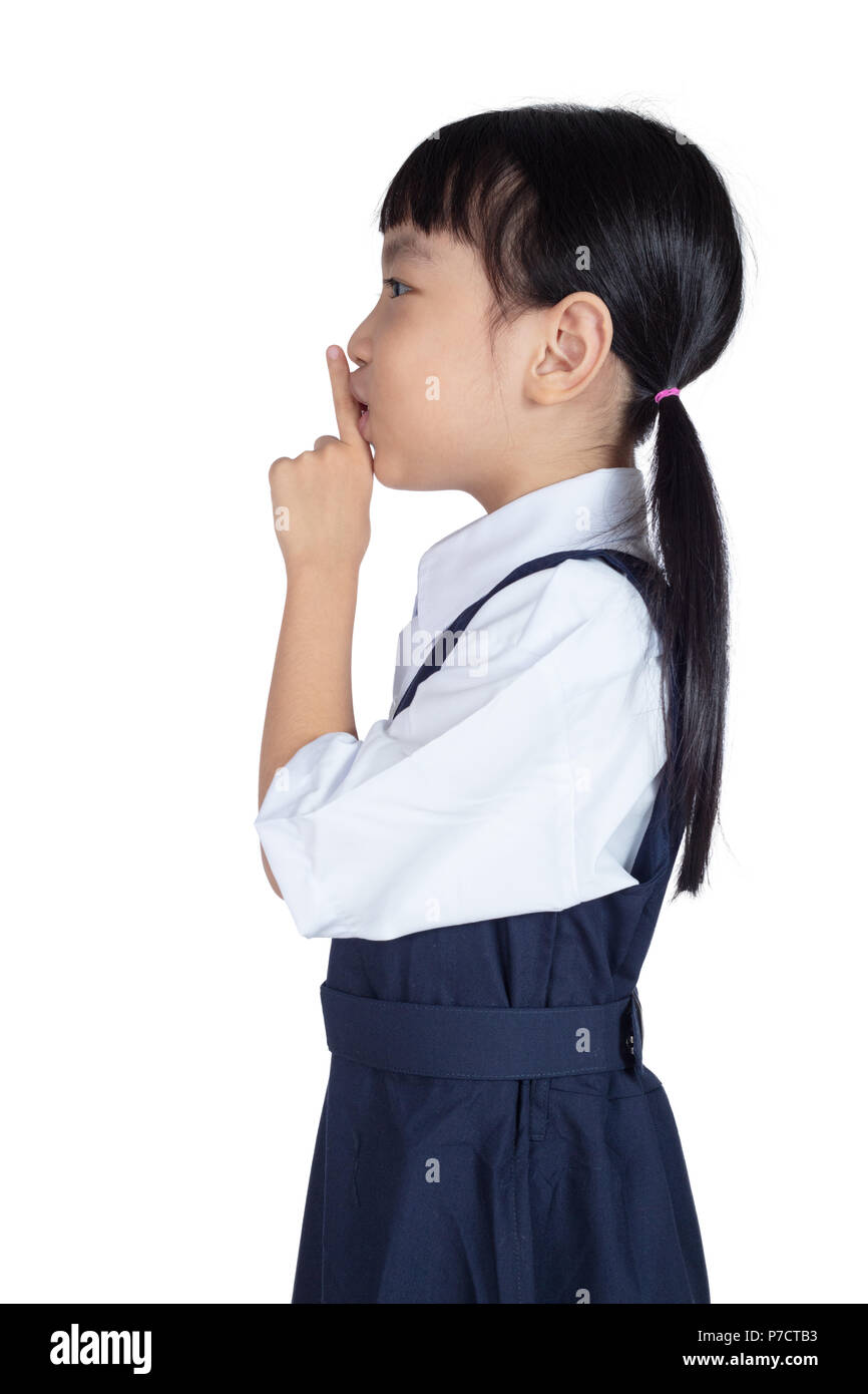 Asian Little Chinese Girl putting finger up to lips and asking for silence in isolated White Background - Stock Image