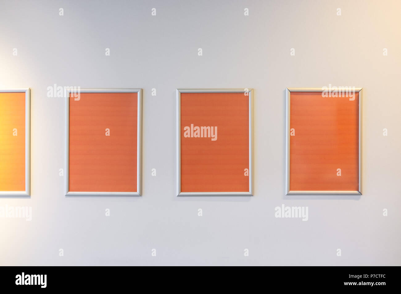 Row of empty vertical picture frames hanged on white wall with copy space - Stock Image