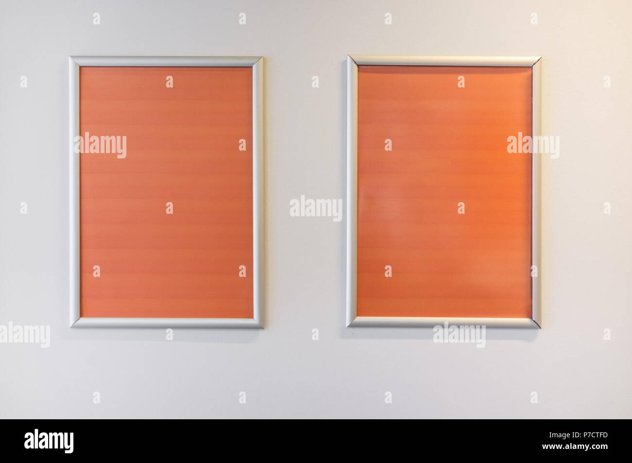 Two picture frames with orange copy space hanging on white wall - Stock Image