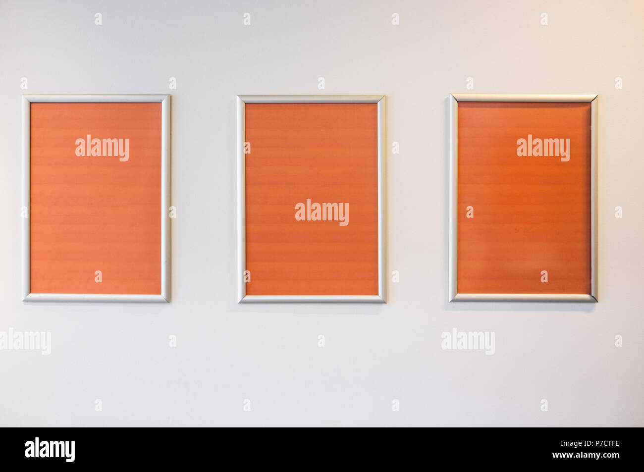 Three picture frames with orange copy space hanging on white wall - Stock Image