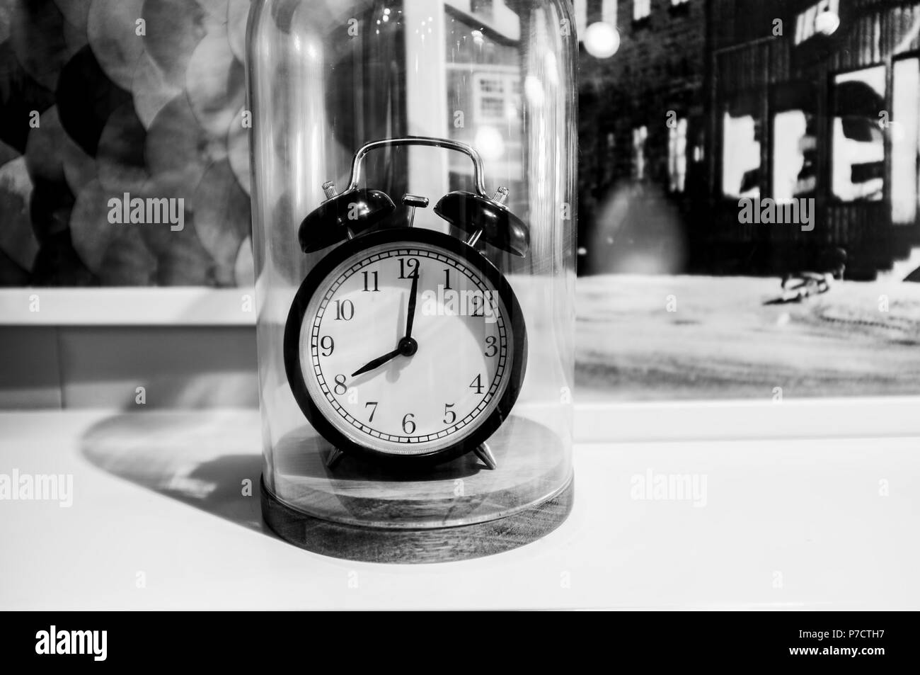 Retro alarm clock showing 8 O'clock on blurred background in black and white - Stock Image