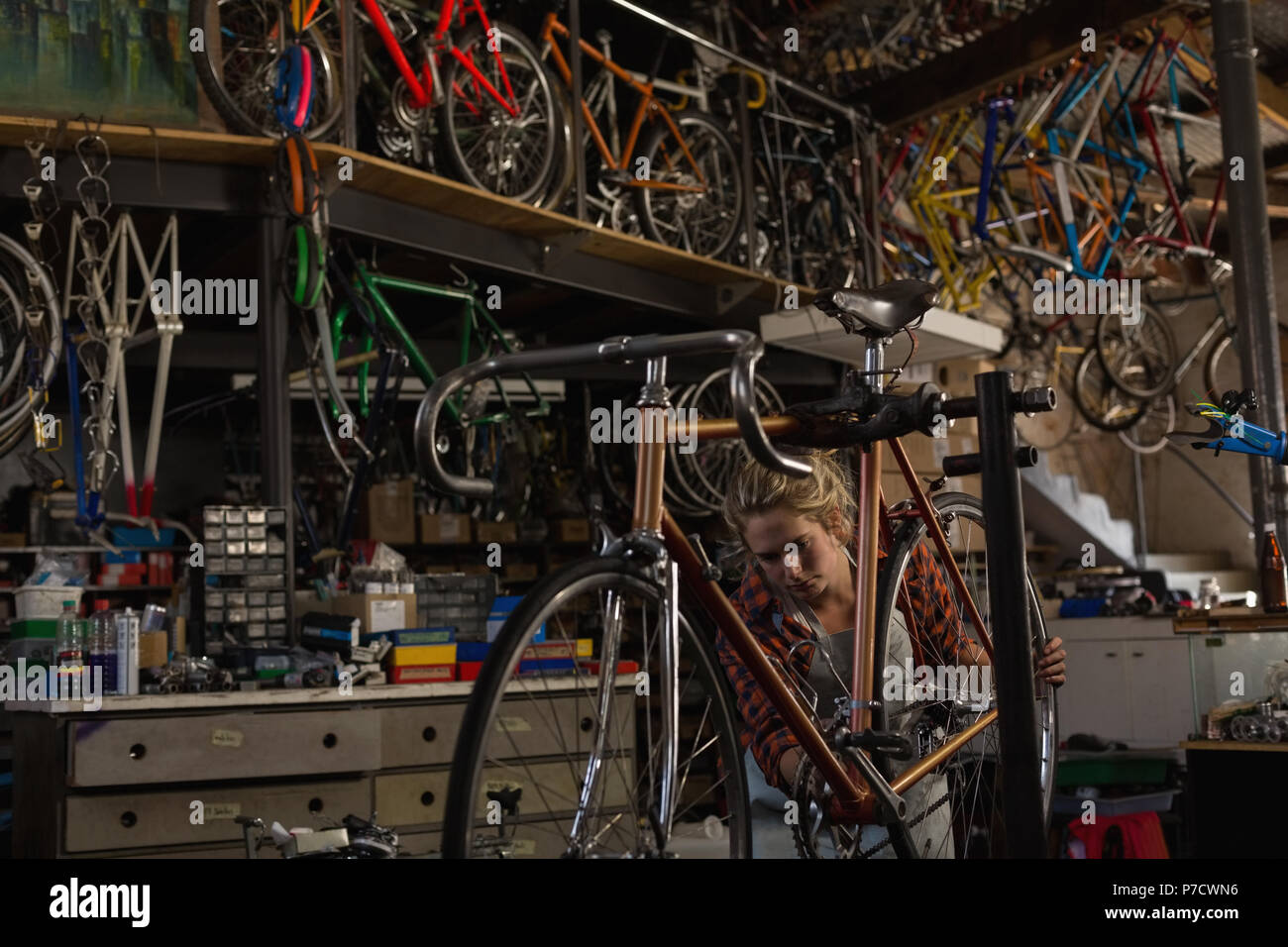 Female mechanic examining a bicycle - Stock Image