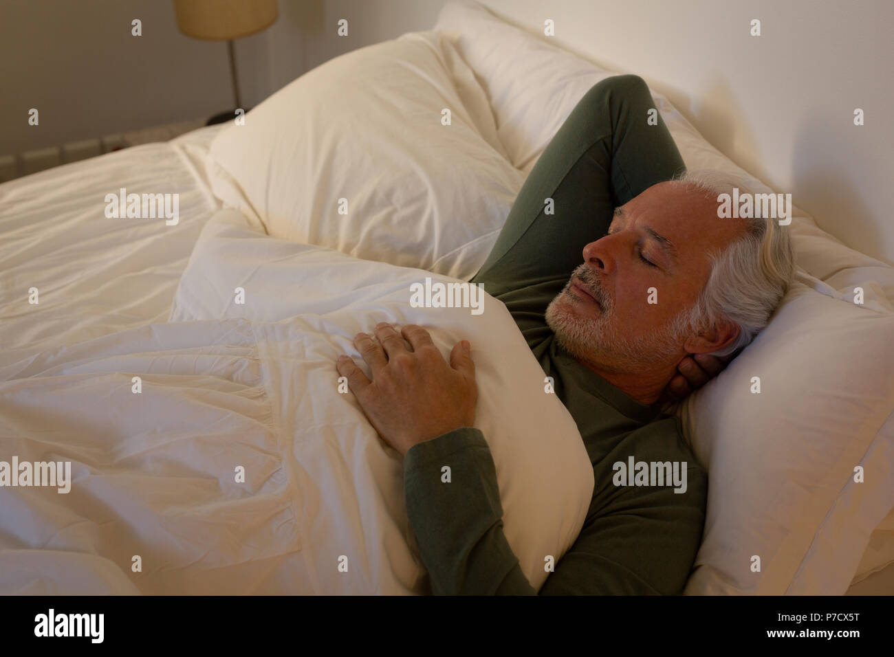 Senior man sleeping in bedroom - Stock Image