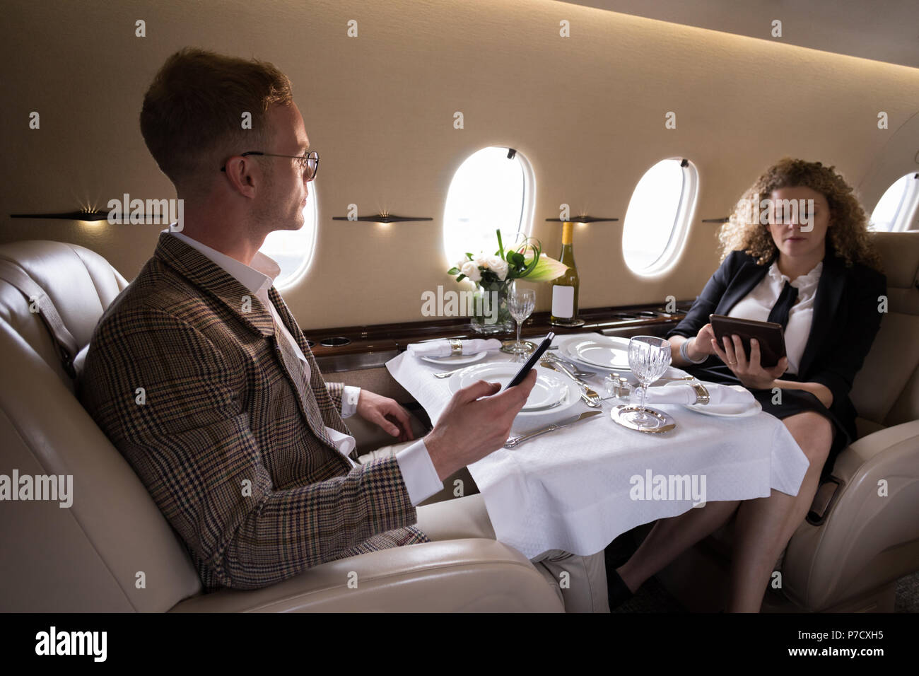 Businesspeople using mobile phone and digital tablet - Stock Image