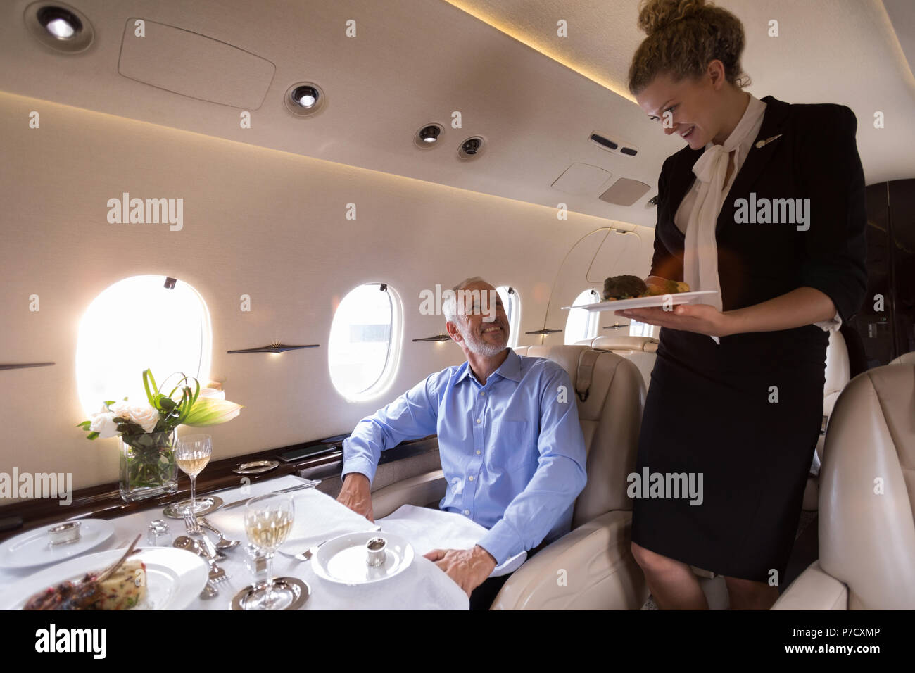 Flight attendant serving meal to businessman - Stock Image