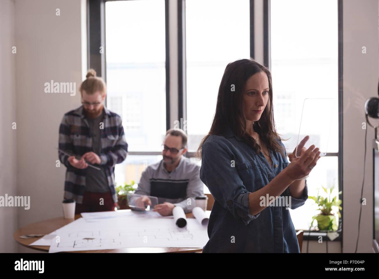 Female executive using glass digital tablet - Stock Image