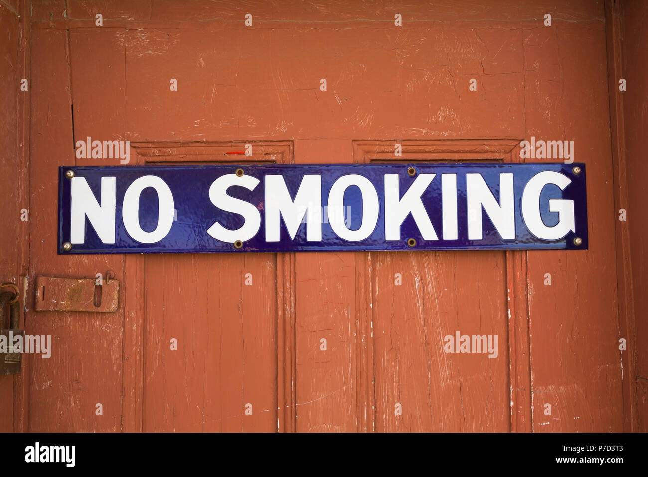 White and blue No Smoking sign on reddish brown wooden entrance door, background image - Stock Image