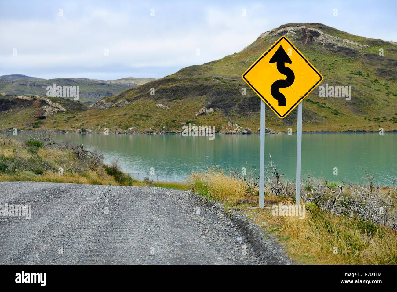 Sign Attention curves along the natural road, Laguna Amarga, Torres del Paine National Park, Última Esperanza Province, Chile - Stock Image