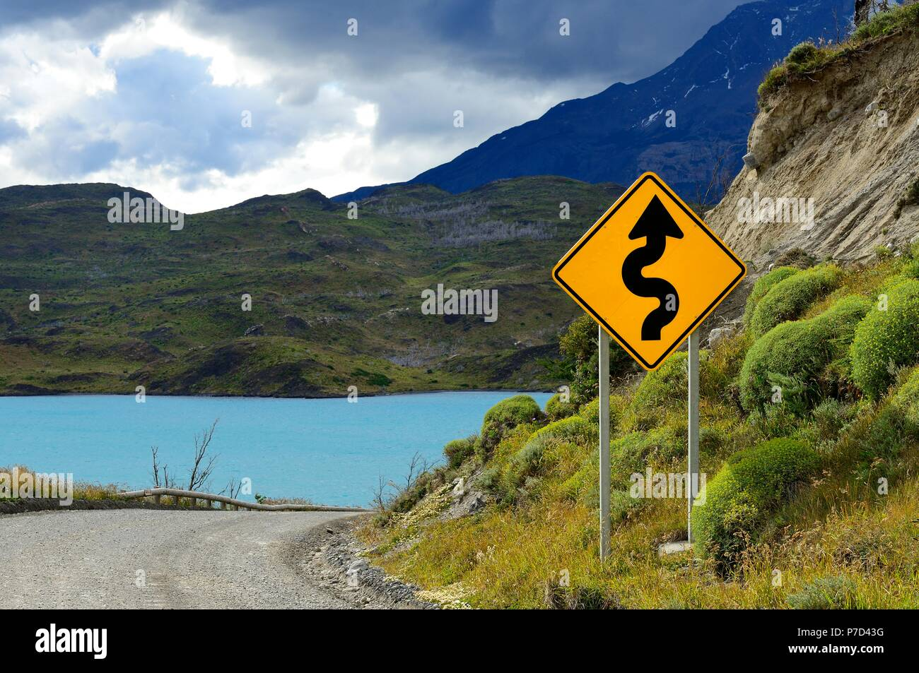 Road Sign Attention curves at Lago Pehoe, Torres del Paine National Park, Última Esperanza Province, Chile - Stock Image