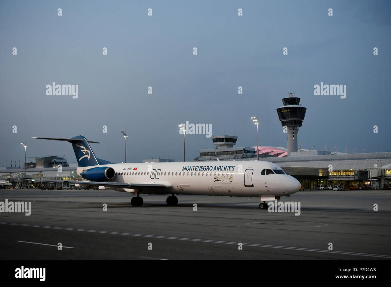 Montenegro Airlines, Fokker, F100, taxiing in front of Terminal 1 with tower, at dusk, Munich Airport, Upper Bavaria, Bavaria Stock Photo