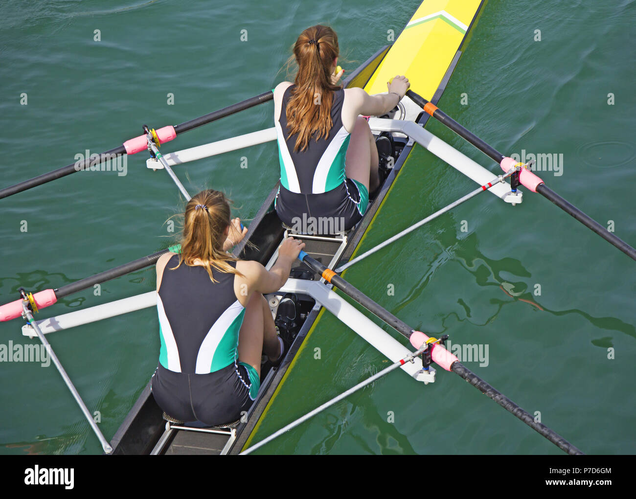 Two young women rowing race in lake - Stock Image