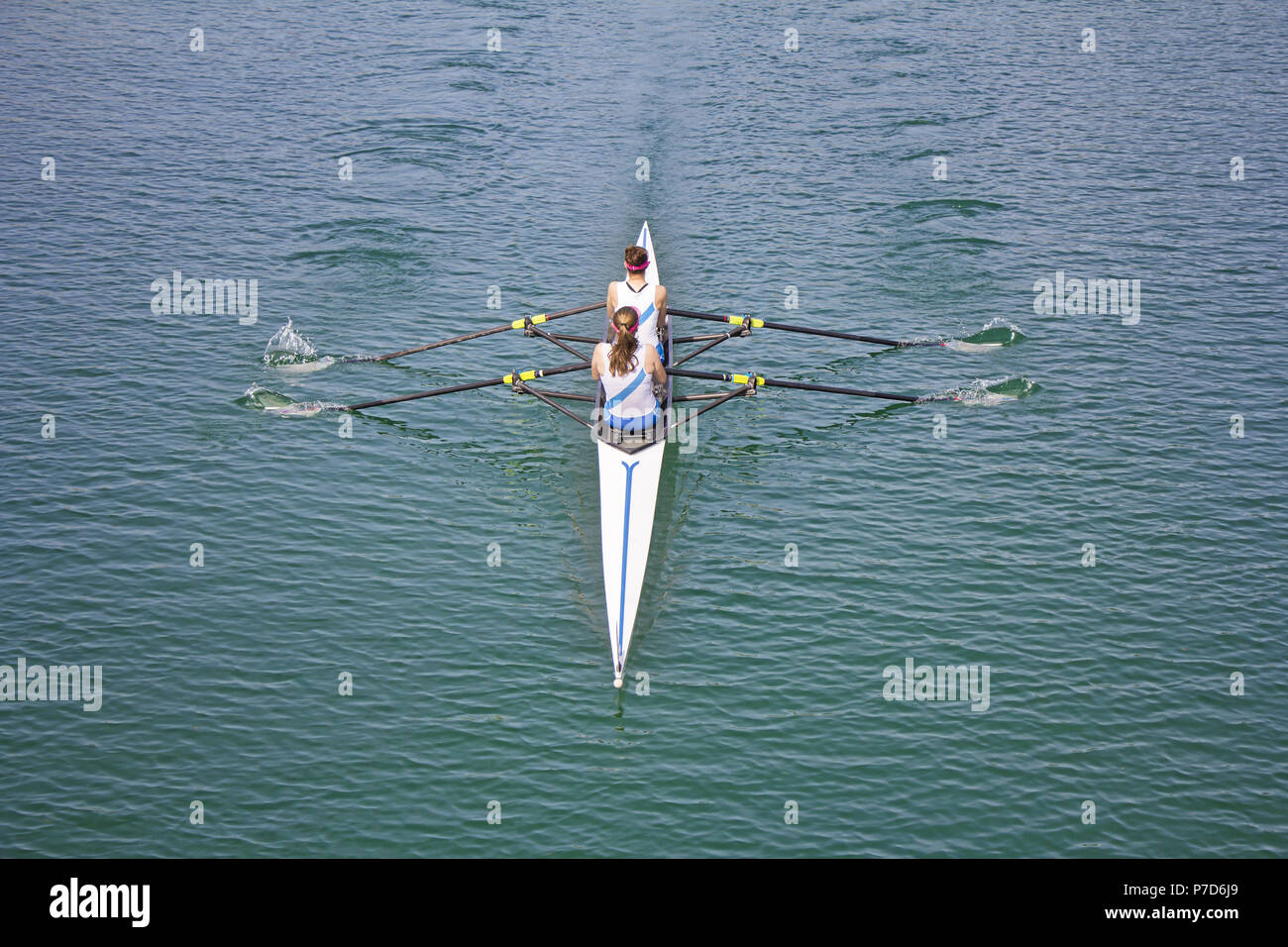 Two young women rowing race in lake Stock Photo