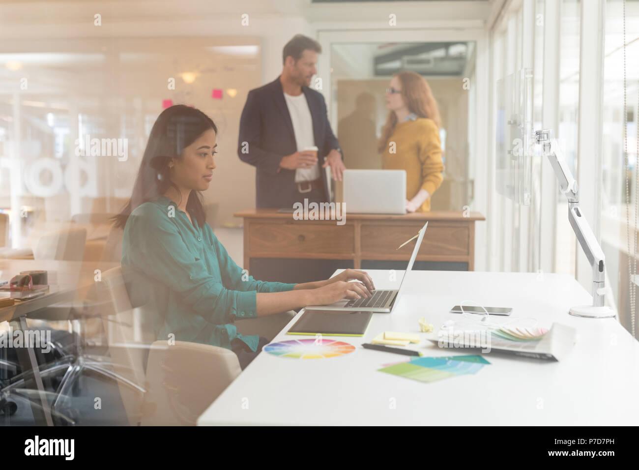 Female graphic designer using laptop at desk - Stock Image