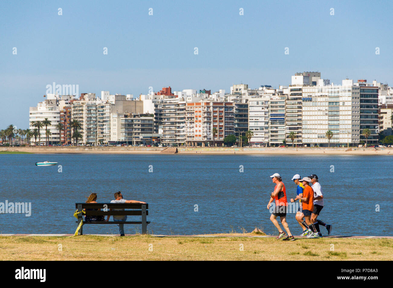 Joggers and people on a bench at the Rambla, promenade of Montevideo, Uruguay - Stock Image