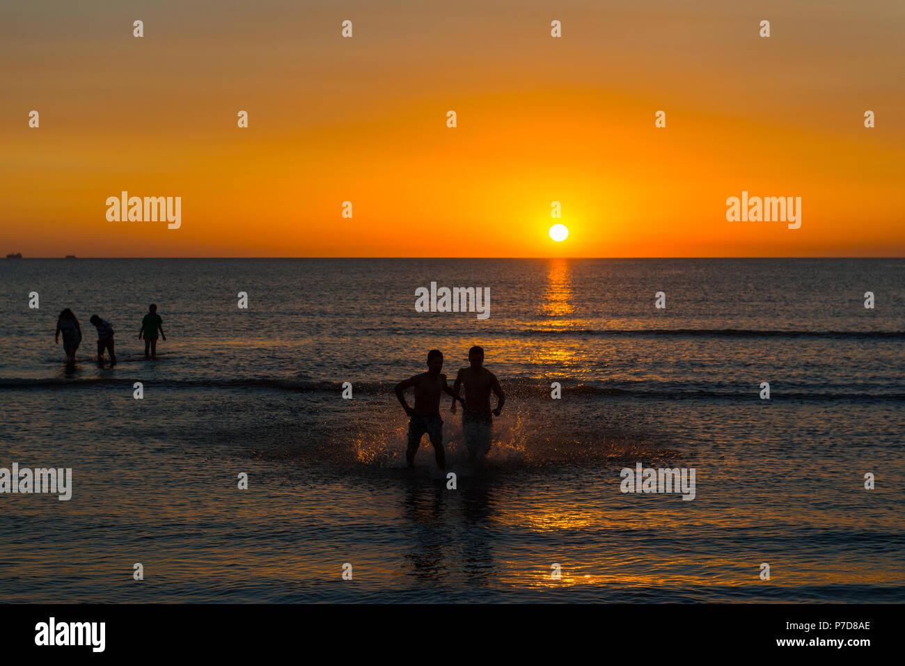Silhouette, swimmers at sunset at the Rio de la Plata, city beach of Montevideo, Uruguay - Stock Image