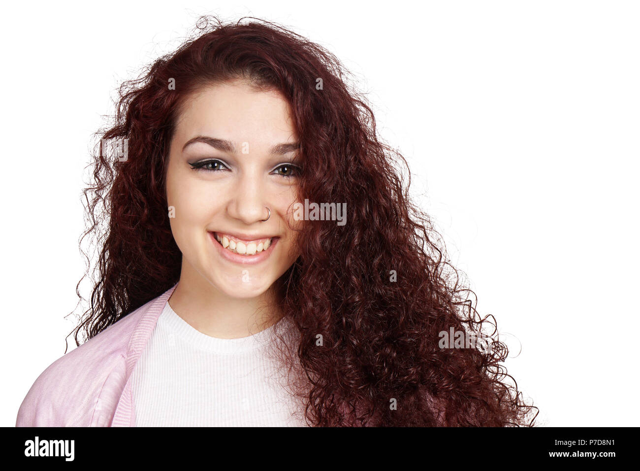 happy teenage girl with long curly hair and toothy smile isolated on white - Stock Image