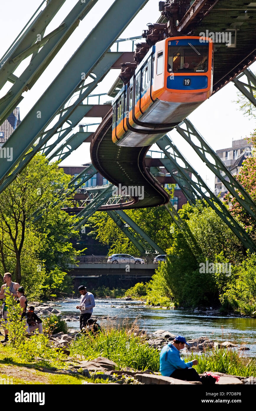 People on the river Wupper with moving suspension railway over it, Wuppertal, Bergisches Land, North Rhine-Westphalia, Germany - Stock Image